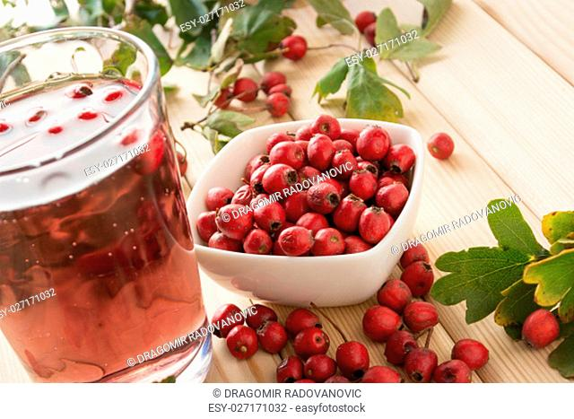 Drink From Dried Hawthorn Berries served on the table sorrounded by hawthorn leaves