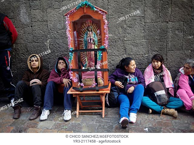 Pilgrims sit by an image of the Virgin of Guadalupe at the pilgrimage to Our Lady of Guadalupe Basilica in Mexico City, Mexico, December 10, 2013