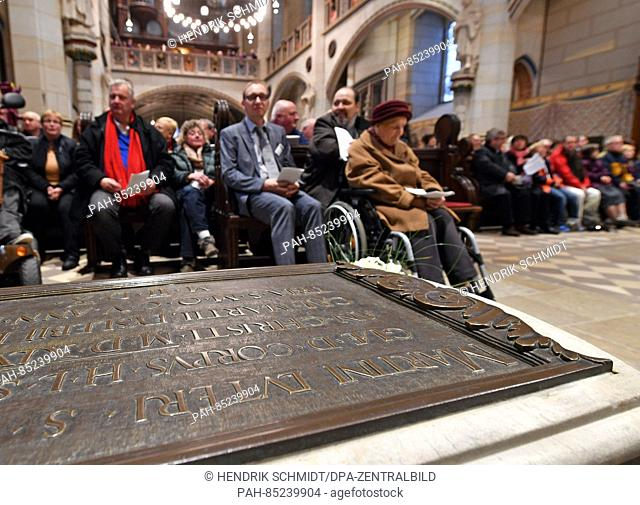 Participants in a church service on Reformation Day sit behind the grave of Martin Luther in the renovated All Saints' Church in Wittenberg, Germany