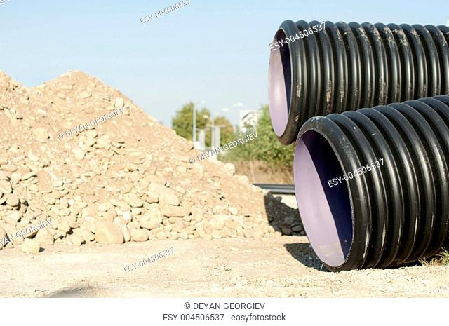 Pipes and piles of sand in the background