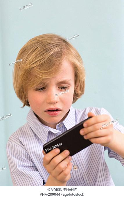 7 year old boy playing with a smartphone