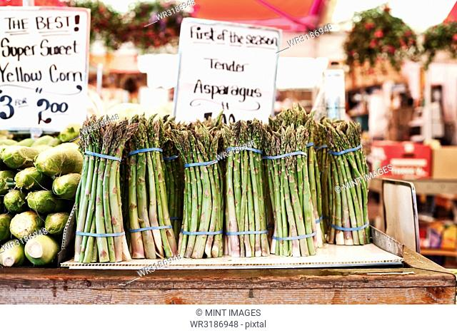 Close up of stacks of fresh green asparagus at a fruit and vegetable market