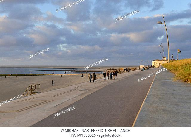 Holidaymaker on Borkum's promenade in the evening light with view to the beach under a cloudy sky, 29 October 2016 | usage worldwide