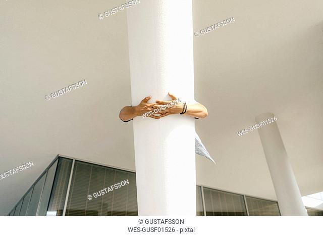Netherlands, Maastricht, hands of a man clutching column of a building