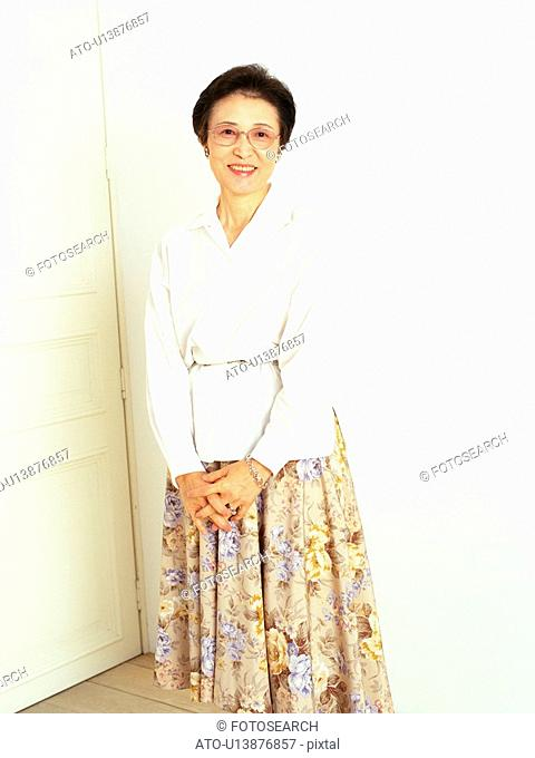 Senior woman standing in front of a white door, looking at camera, Smiling, Front View