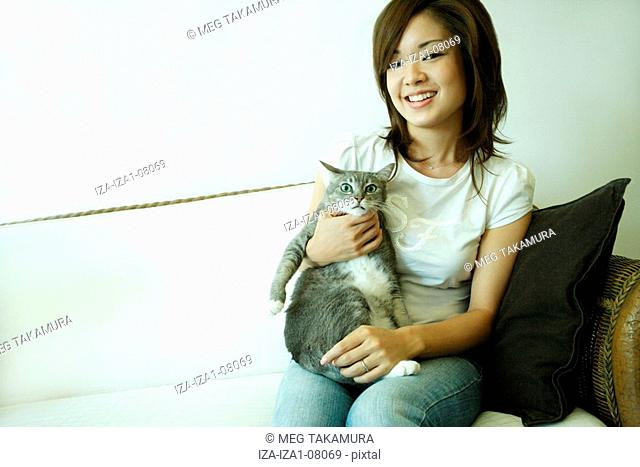 Portrait of a young woman carrying a cat and sitting on a couch