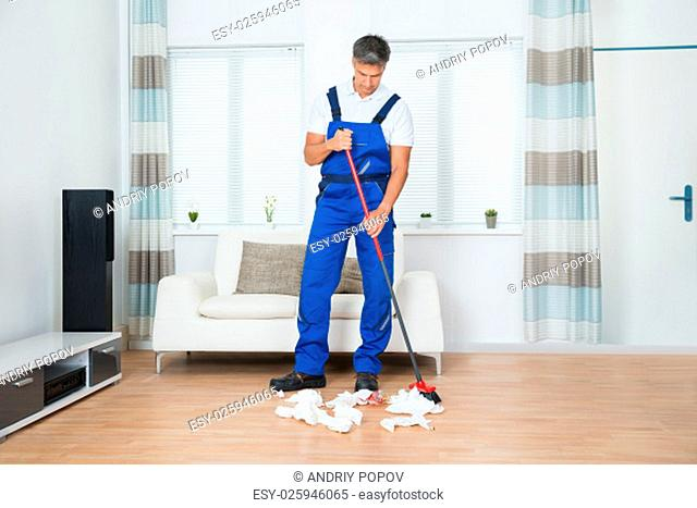 Full length of male janitor sweeping crumpled papers on floor in living room