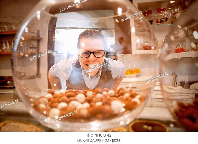 Cashier smiling behind glass bowl