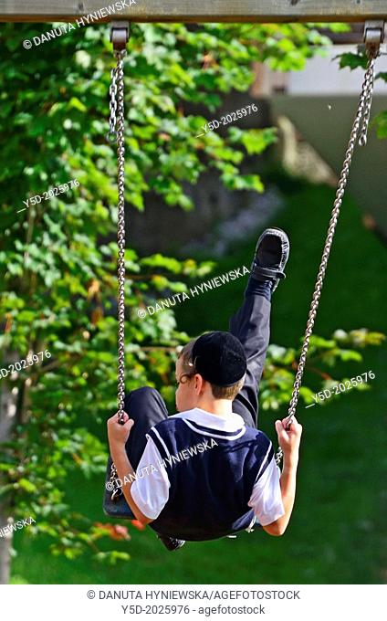 single Jewish boy in traditional clothes swinging on a swing