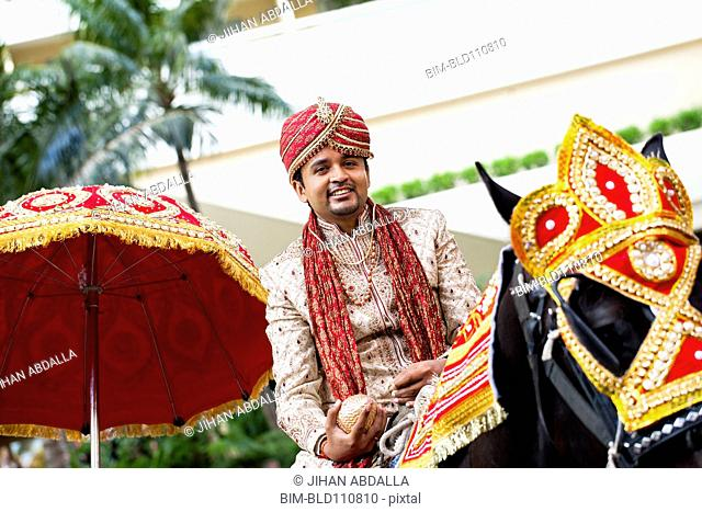 Indian groom riding horse in wedding procession