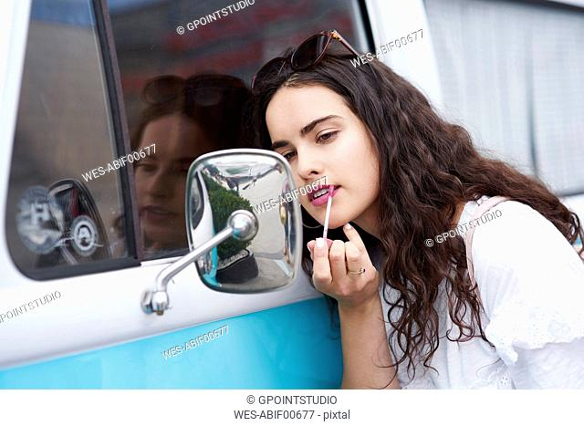 Young woman applying lipstick looking in wing mirror of a van