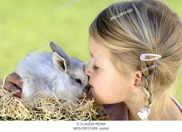 Girl 6-7 kissing Easter bunny, close-up, side view