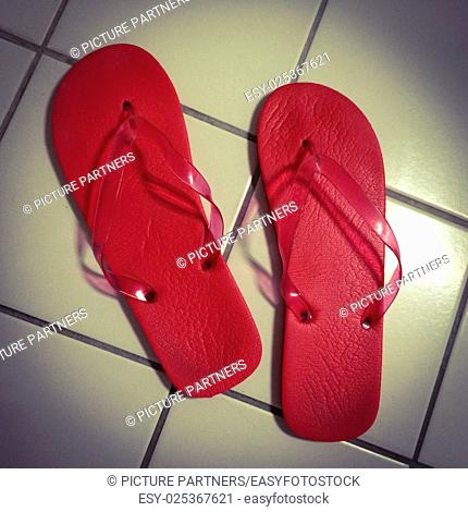 Red bath flip flops on white tiles in the bathroom