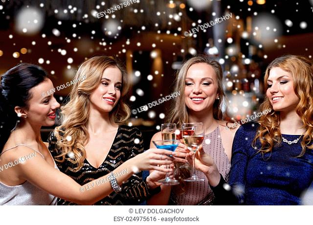 celebration, friends, new year, christmas and winter holidays concept - happy women drinking champagne and cocktails at bachelorette party at night club over...
