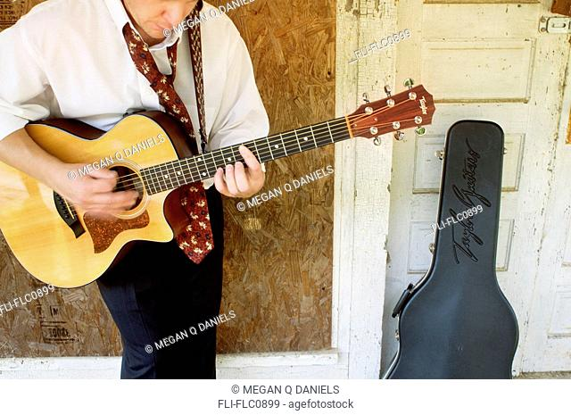 A 38-year-old Caucasian man playing a 314CE Taylor Guitar outside a run-down house in Bynum, North Carolina, USA