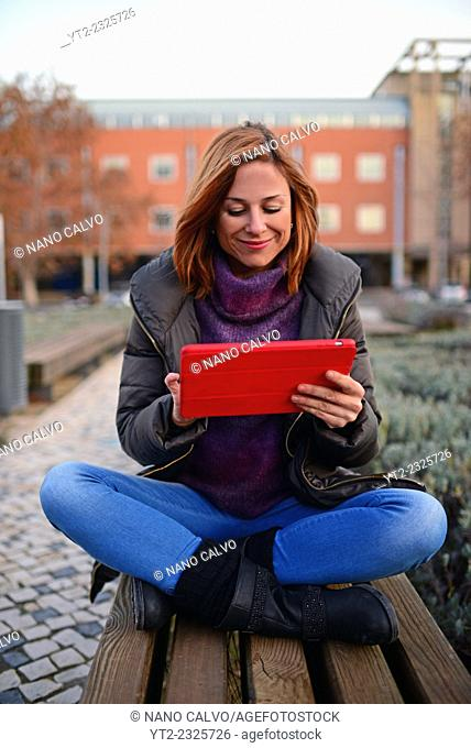 Attractive young woman using tablet outdoors