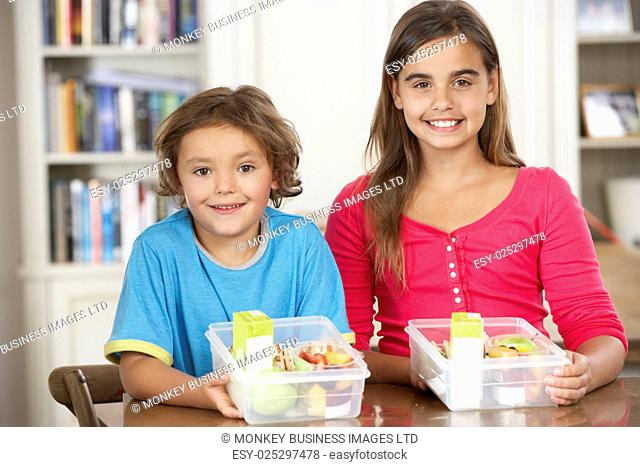 Two Children With Healthy Lunchboxes In Kitchen