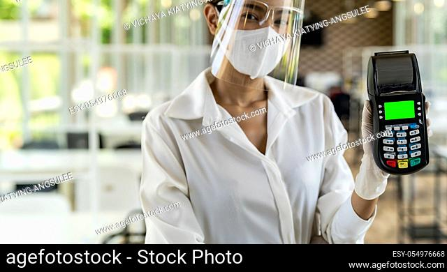 Portrait attractive asian waitress wear face mask and face shield hold credit card reader for contactless payment with indoor restaurant background