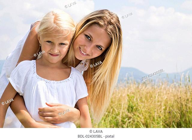 portrait of young woman and daughter in meadow
