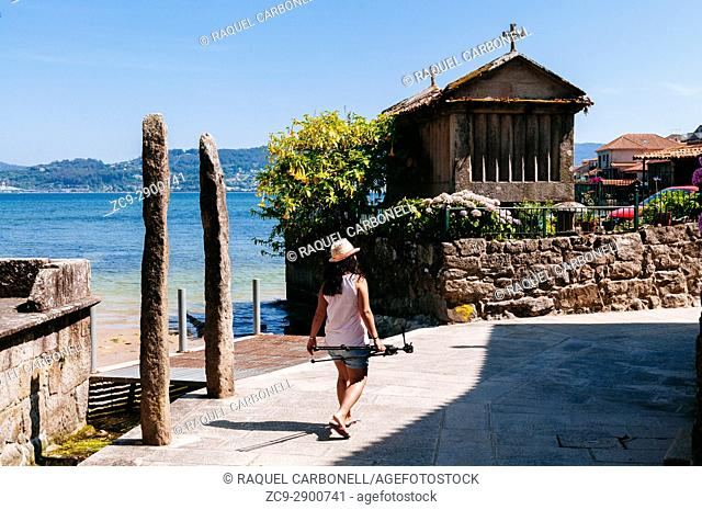 Woman walking by a horreo, traditional stone granary