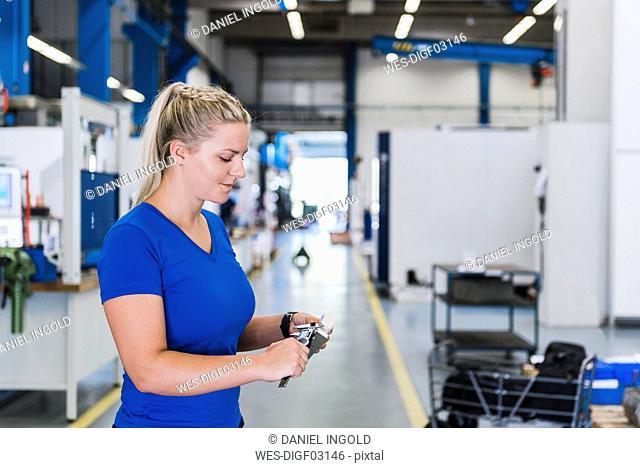 Woman measuring metal workpiece in industrial factory