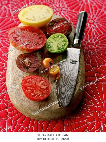 Various juicy sliced tomatoes on cutting board with knife
