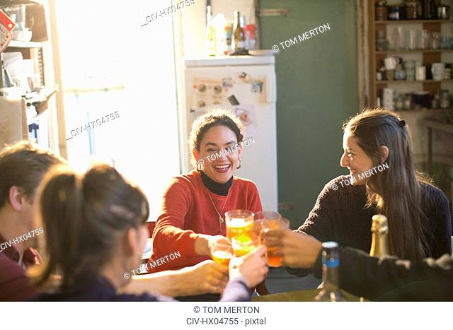 Young adult friends toasting cocktails in apartment kitchen
