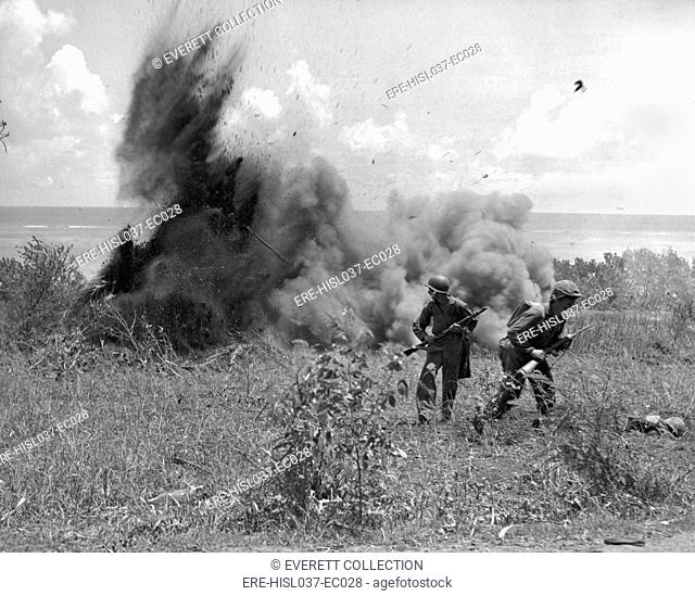 U.S. Marines just after throwing a TNT charge into a Japanese dugout in Saipan. One Marine escapes the blast by crouching in a shell hole