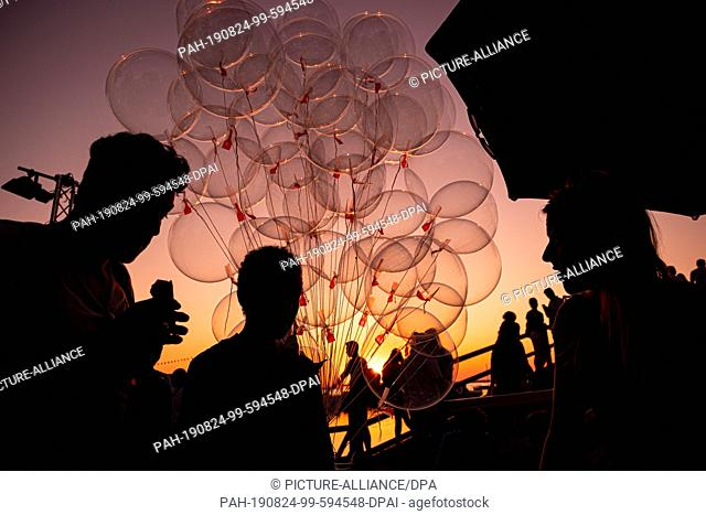 dpatop - 24 August 2019, Lower Saxony, Steinhude: Balloons are to be seen in the sunset on the promenade at the Steinhuder Meer before the beginning of the...