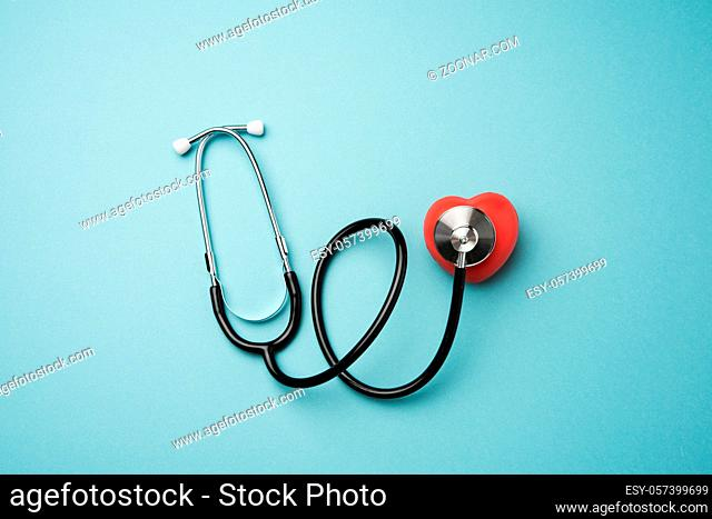 medical stethoscope and red rubber heart on blue background, top view