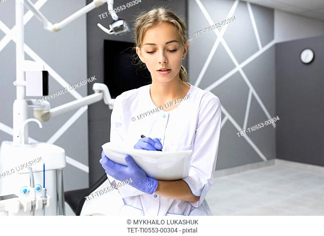 Dental assistant writing notes