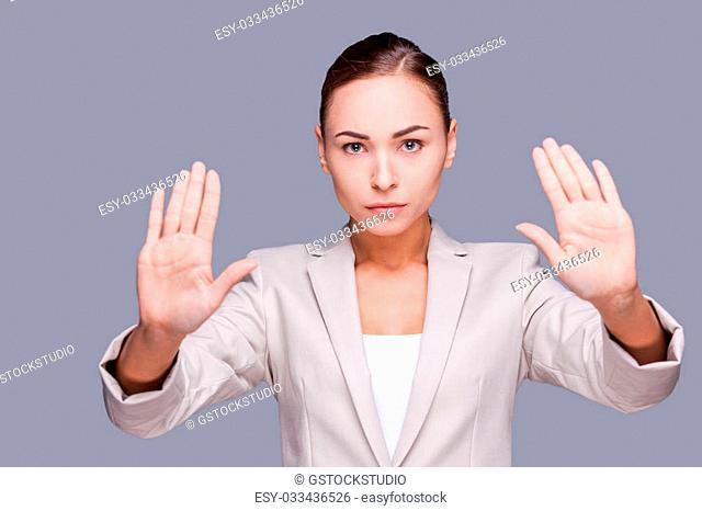 Stop it! Confident young businesswoman gesturing stop sign while standing against grey background