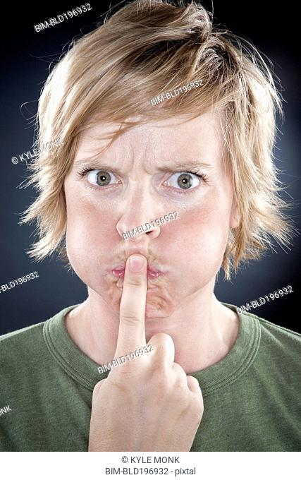 Caucasian woman holding finger over her mouth
