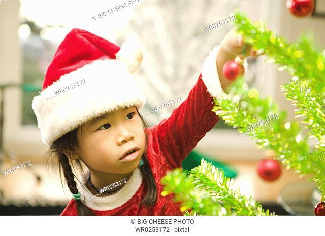 Girl carefully decorating Christmas tree