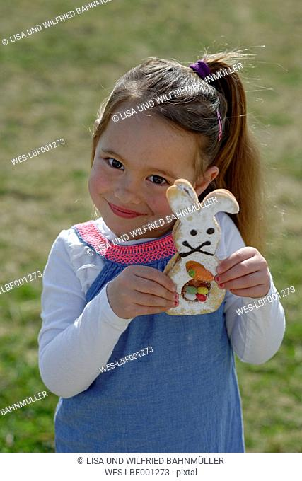 Portrait of smiling little girl showing pastry formed like an Eastern Bunny