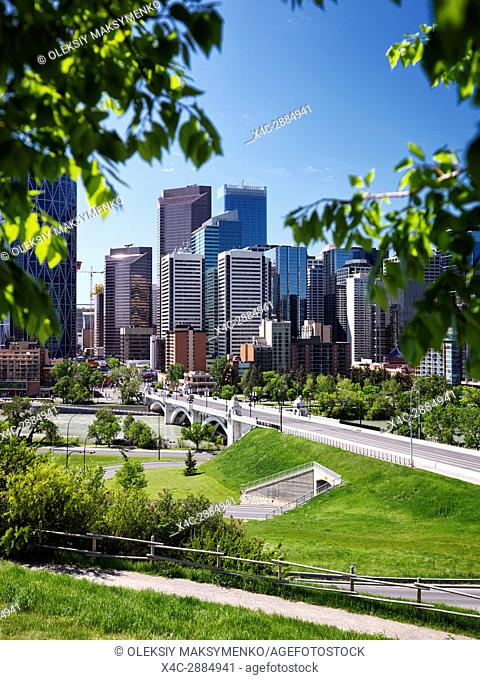 Artistic summertime scenery of Calgary city downtown skyline view and Centre Street Bridge over Bow river framed by green tree leaves