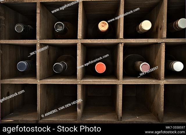 Collection of wine in wooden wine rack in a wine cellar, retro vintage wooden rack design background, close-up