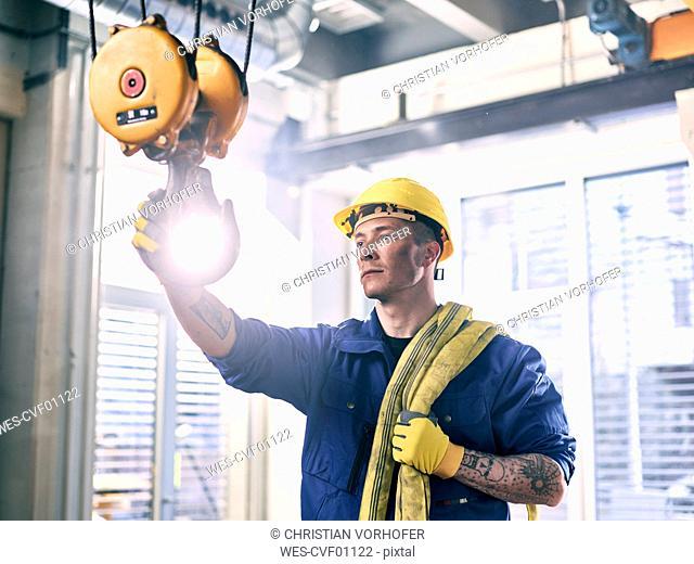 Industrial worker fixing hoist sling on indoor crane