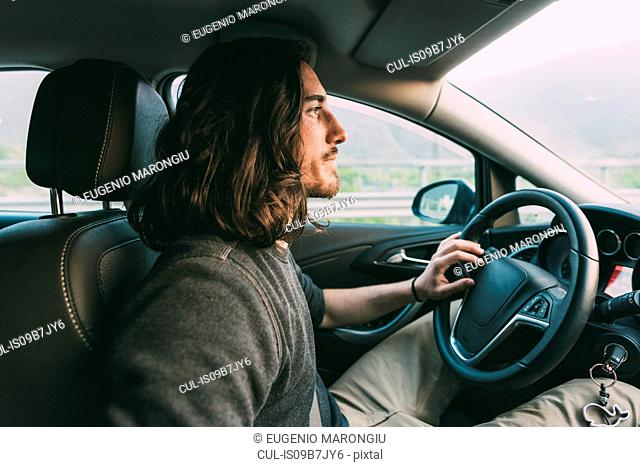 Young man driving car on rural road