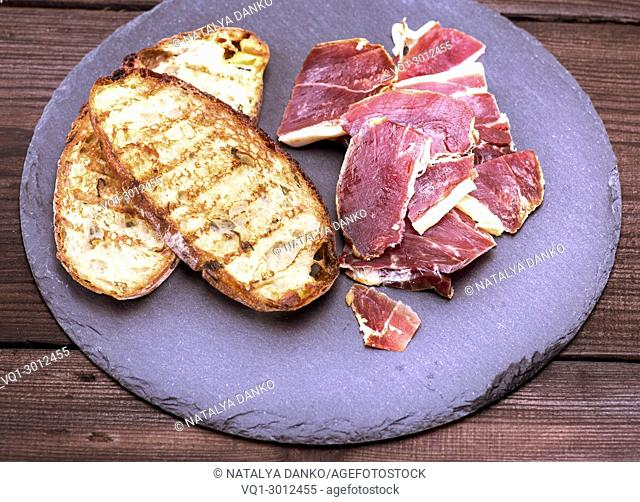 toast of white bread and pieces of jamon on a black plate, top view
