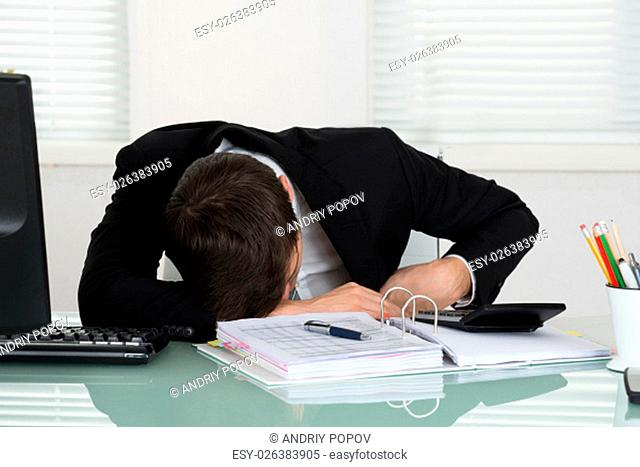 Young Businessman Sleeping With Invoices On Desk In Office