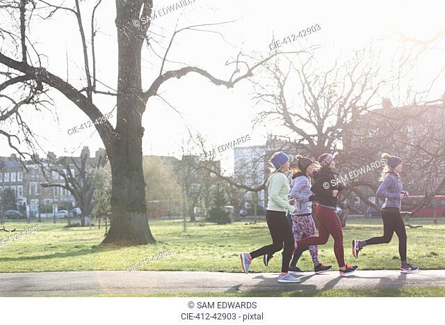 Female runners running in sunny park