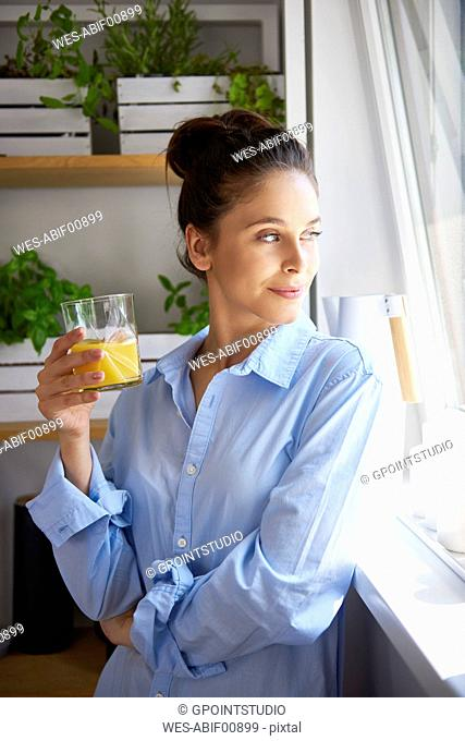 Young woman drinking orange juice in her kitchen