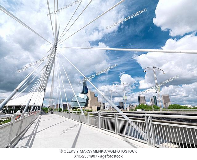 Esplanade Riel Footbridge with the Canadian Museum for Human Rights and downtown skyline under beautiful cloudy sky in the background