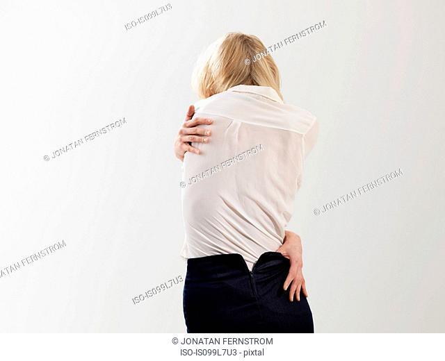 Woman embracing and undressing self, studio shot
