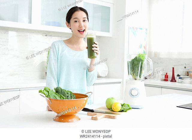 Portrait of young smiling woman holding green vegetable juice