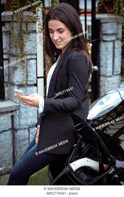 Beautiful woman using mobile phone while charging electric car