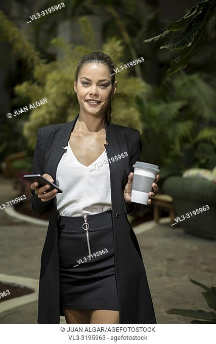 Beautiful fit woman in elegant black suit holding coffee cup and smartphone while smiling at camera in sunlight