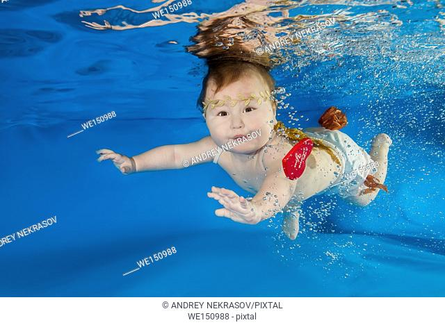 Litle girl in angel costume posing under water in swimming pool, Odessa, Ukraine