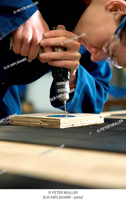 Worker using drill in factory